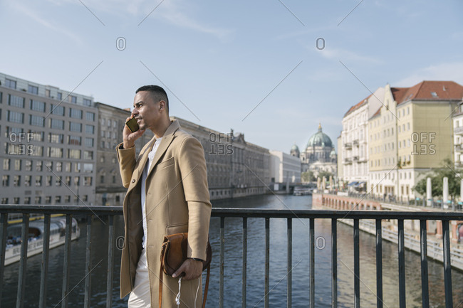 Businessman on the phone standing on a bridge- Berlin- Germany