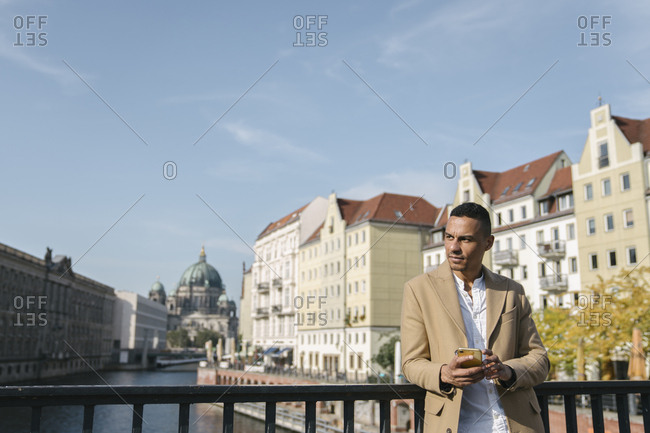 Portrait of businessman standing on a bridge with smartphone looking at distance- Berlin- Germany