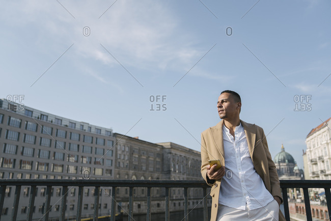 Businessman standing on a bridge with smartphone looking at distance- Berlin- Germany