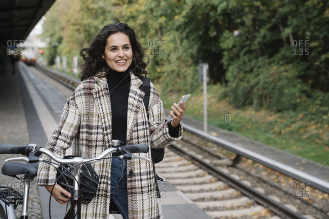 Smiling woman with bicycle and cell phone on an underground station platform- Berlin- Germany