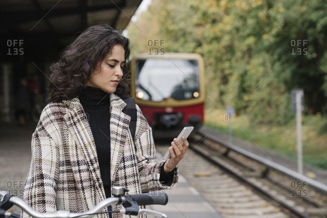 Woman with bicycle and cell phone on an underground station platform- Berlin- Germany
