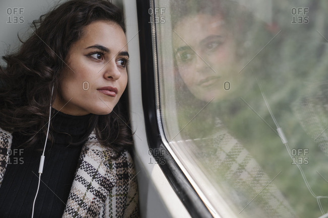 Young woman with earphones on a subway looking out of window
