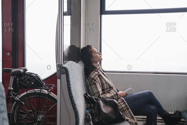 Young woman with closed eyes relaxing on a subway