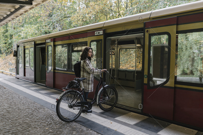Woman with bicycle entering an underground train- Berlin- Germany