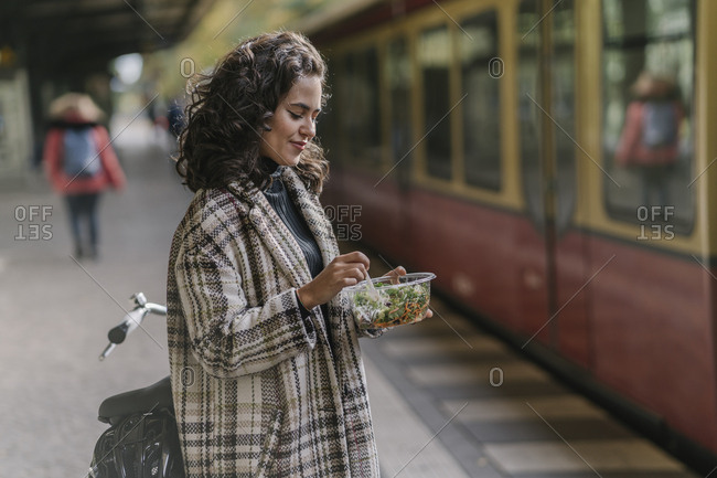 Woman having lunch on an underground station platform- Berlin- Germany