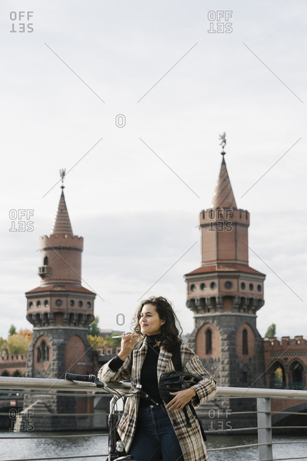 Smiling woman with bicycle using smartphone in the city at Oberbaum Bridge- Berlin- Germany