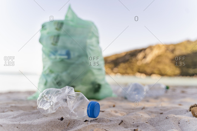 Empty plastic bottles and garbage bin full of collected plastic bottles on the beach