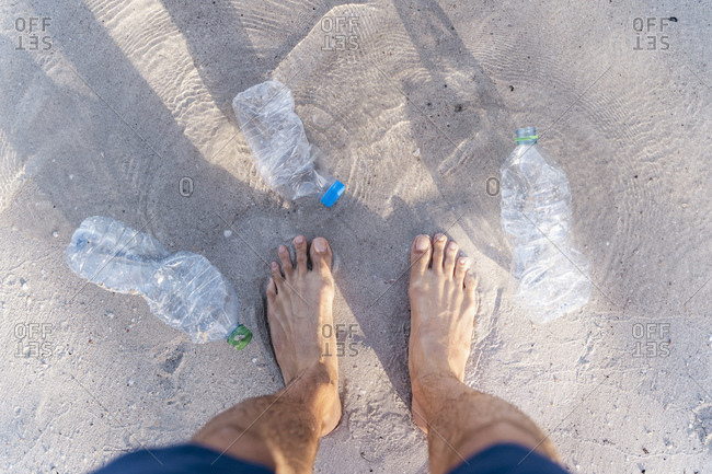 Man's feet on the beach surrounded by empty plastic bottles- top view