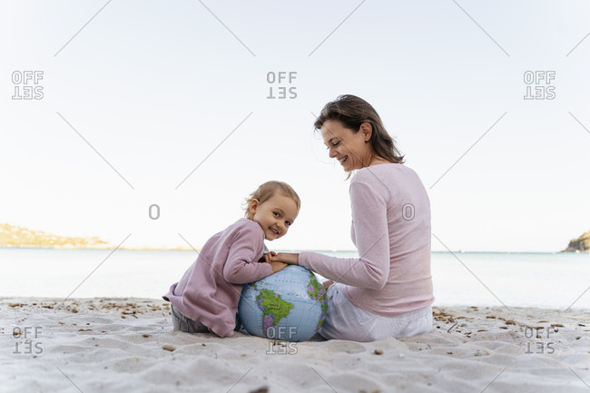 Portrait of happy little girl sitting with her mother on the beach playing with Earth beach ball
