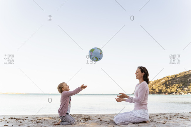 Happy little girl sitting with her mother on the beach playing with Earth beach ball