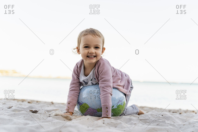 Portrait of happy little girl playing with  Earth beach ball