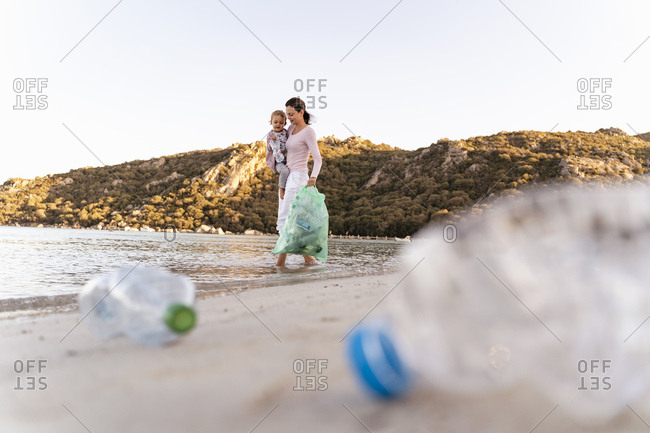 Woman  carrying little daughter on her arm collecting empty plastic bottles at seashore