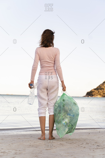 Back view of woman standing on the beach with bin bag of collected empty plastic bottles