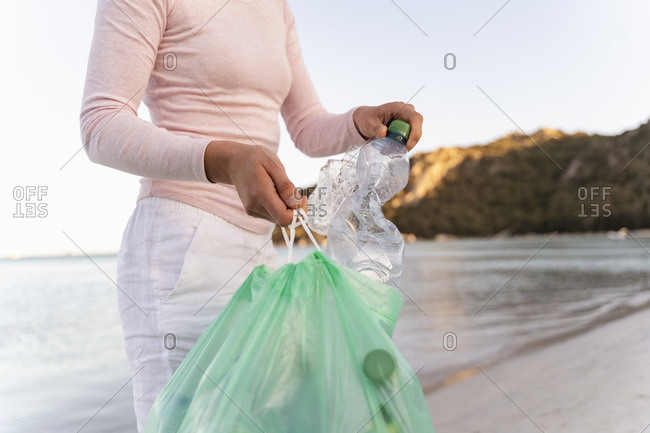Woman collecting empty plastic bottles  on the beach