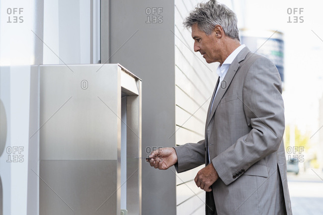 Mature businessman withdrawing money at an ATM
