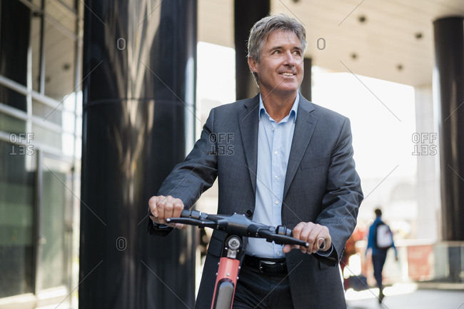 Mature businessman with e-scooter in the city