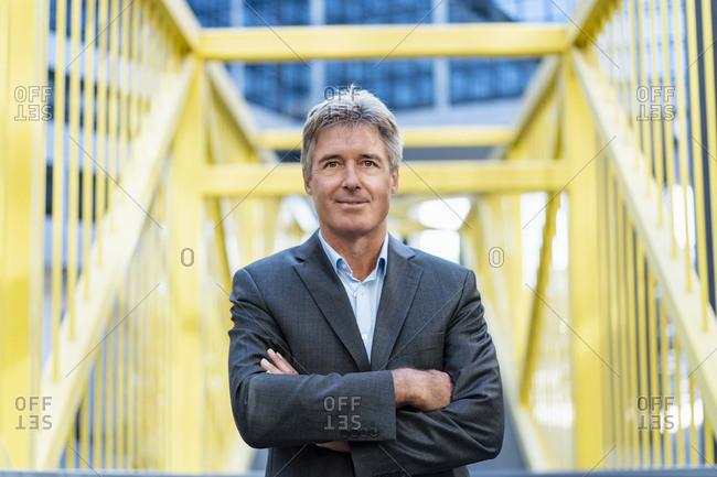 Portrait of confident mature businessman on a bridge