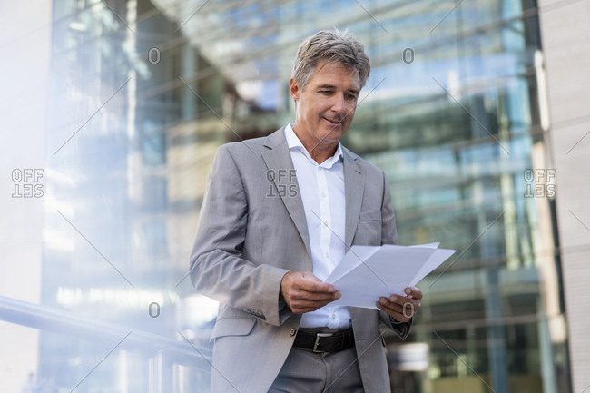 Mature businessman reviewing documents in the city