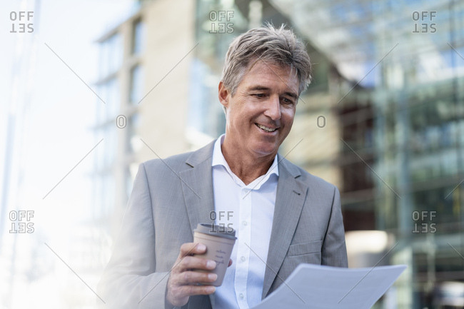 Smiling mature businessman with takeaway coffee reviewing documents in the city