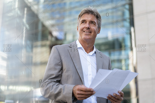 Mature businessman holding documents in the city