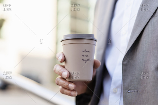 Close-up of businessman holding reusable takeaway coffee cup