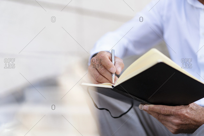 Close-up of businessman sitting on stairs with notebook