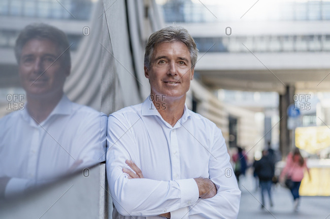 Portrait of confident mature businessman leaning against a glass front in the city