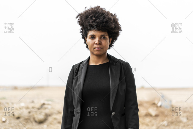Portrait of self-confident young woman dressed in black in bleak landscape