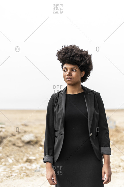 Portrait of self-confident young woman dressed in black standing in bleak landscape
