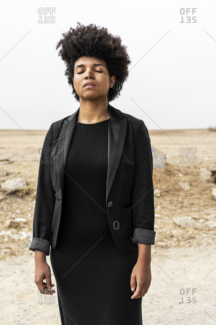 Portrait of young woman dressed in black standing in bleak landscape