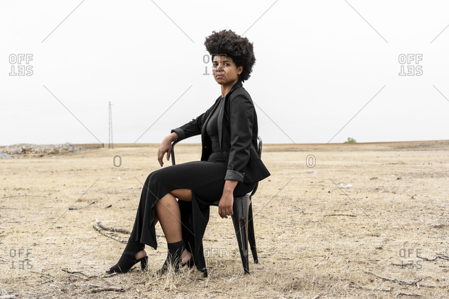 Portrait of young woman dressed in black sitting in bleak landscape
