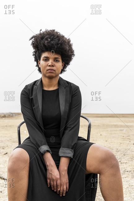 Portrait of young woman dressed in black sitting in bleak landscape