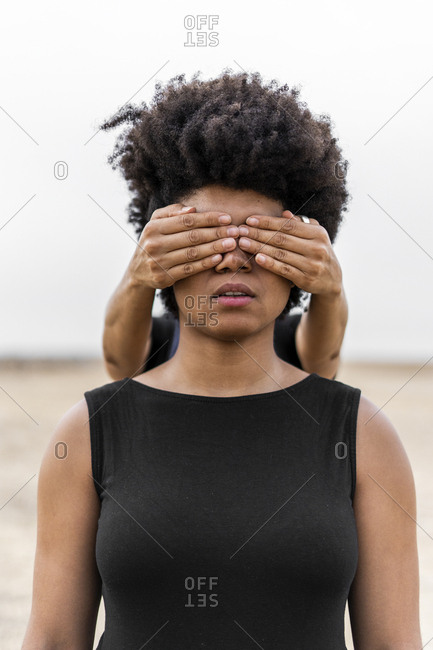 Woman's hands covering eyes of another woman