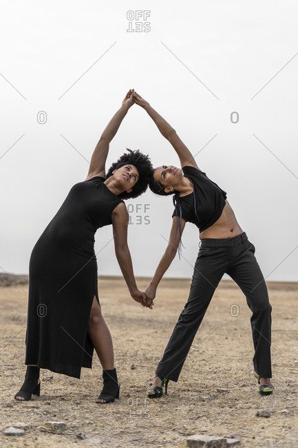 Two women dressed in black performing in bleak landscape