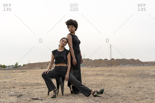 Portrait of two women dressed in black in bleak landscape