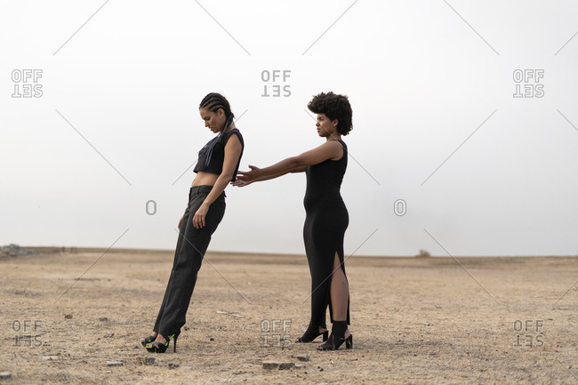Two women dressed in black in bleak landscape