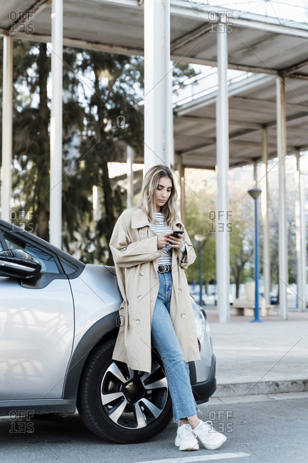 Young blond woman using smartphone- leaning on a car
