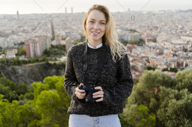Portrait of smiling young woman with camera at sunrise above the city- Barcelona- Spain