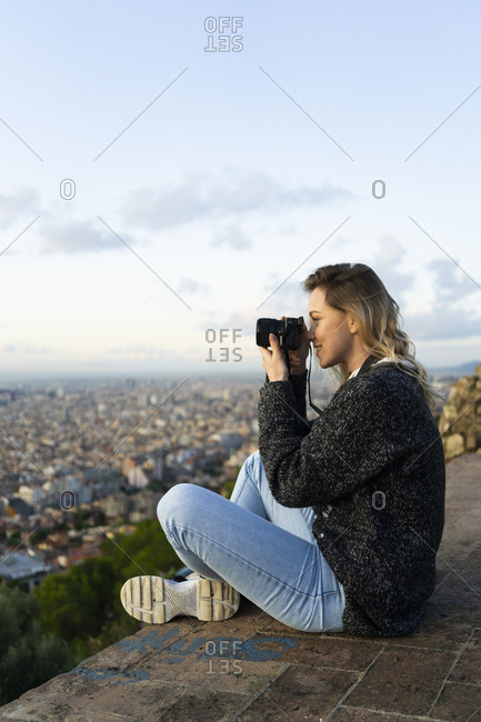 Young woman taking pictures above the city at sunrise- Barcelona- Spain