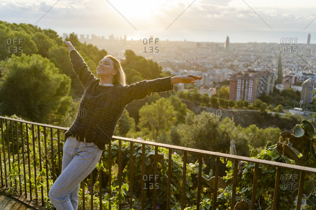 Carefree young woman standing above the city at sunrise- Barcelona- Spain