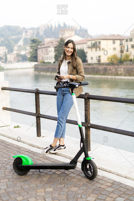 Young woman renting an e-scooter- holding her smartphone in Verona- Italy