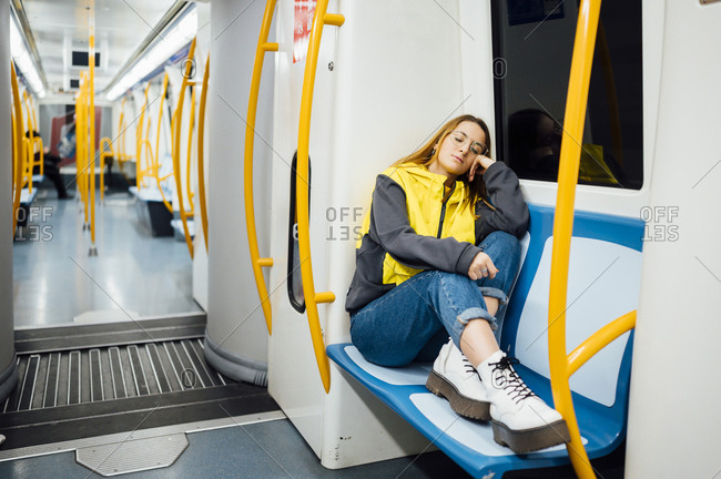 Young woman sleeping in underground train