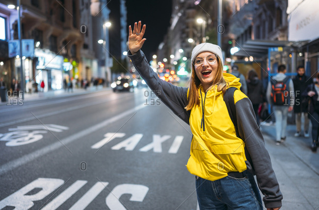 Young woman in the city hailing a taxi at night