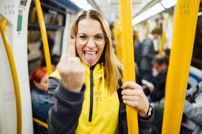 Young woman standing in underground train giving the finger