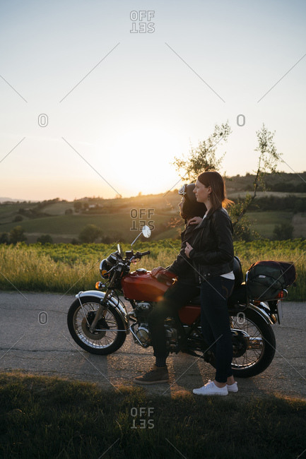 Young couple with vintage motorbike standing on country road at sunset looking at view- Tuscany- Italy