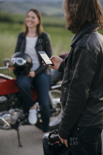 Young motorcyclist standing on country road using smartphone while his girlfriend waiting in the background