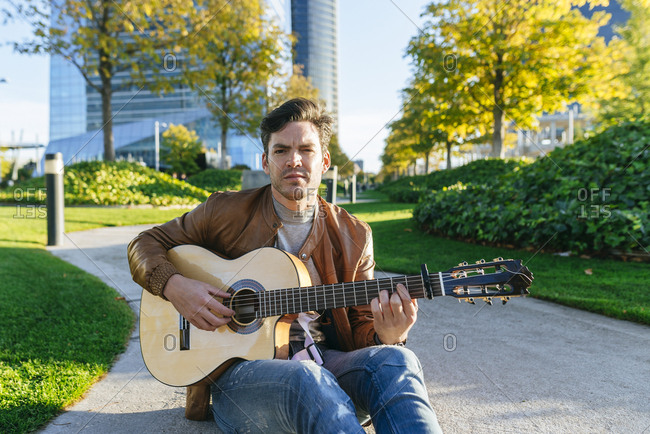 Man playing guitar in an urban park- Madrid- Spain