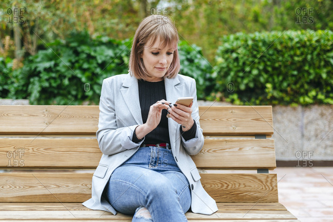 Woman sitting on park bench using cell phone