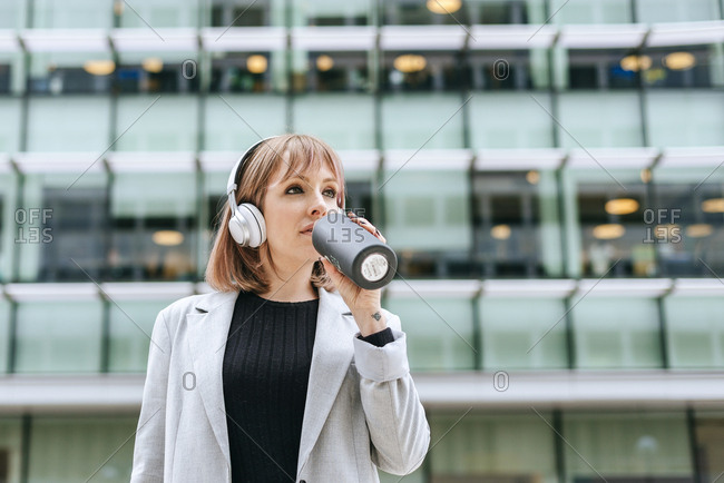 Woman with headphones drinking from reusable bottle in the city