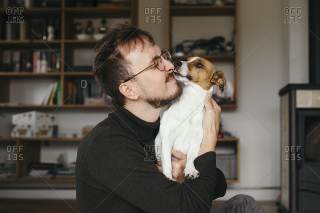 Young man with Jack Russel Terrier- licking